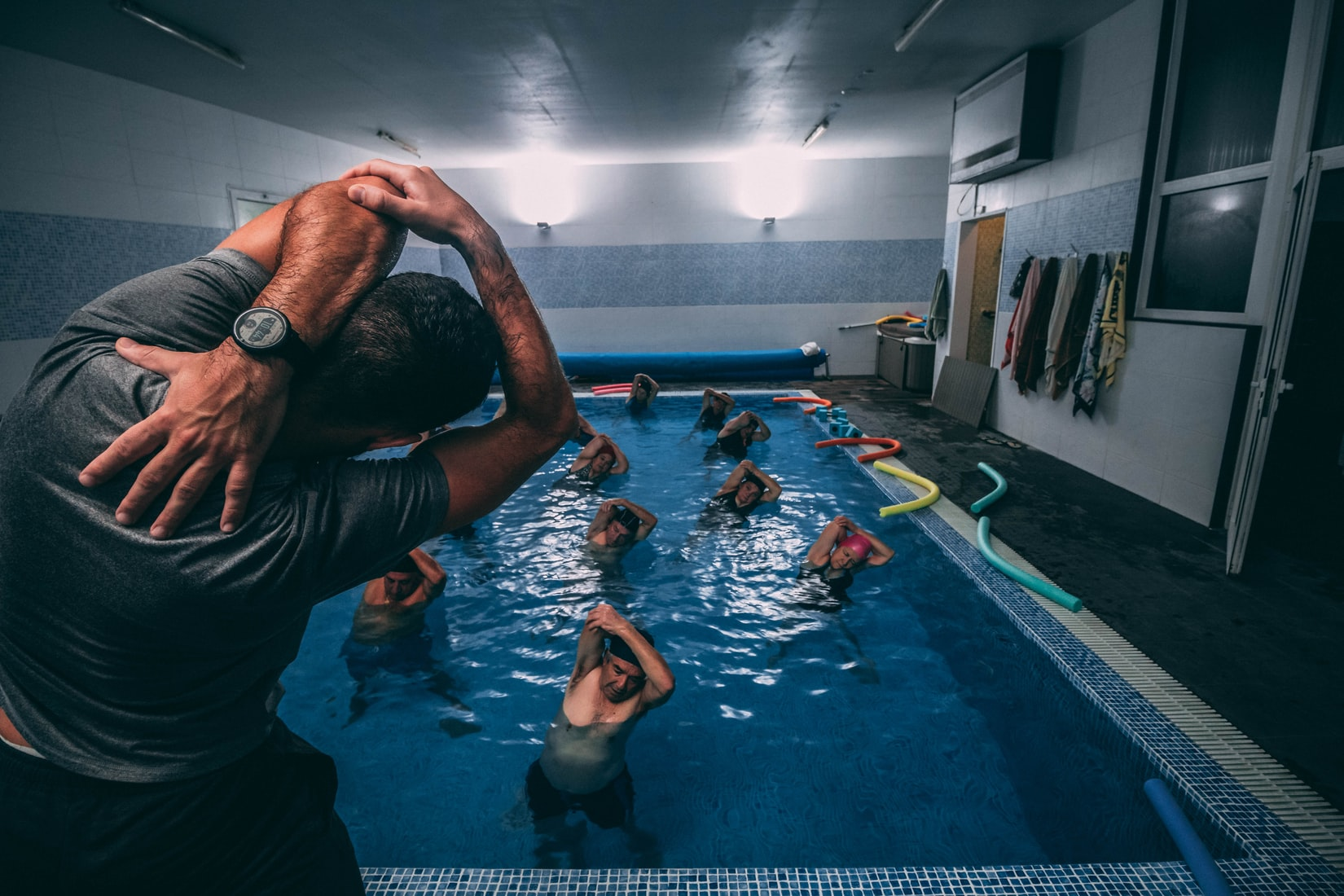 kinesiologist leading stretches for people in pool